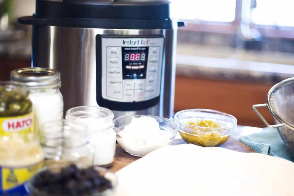 Instant Pot with ingredients for green chile pork burritos