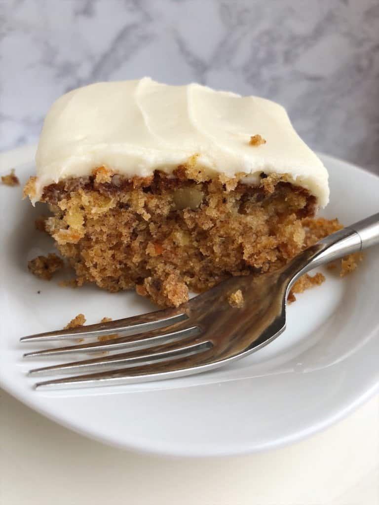 pineapple carrot cake with cream cheese frosting and fork