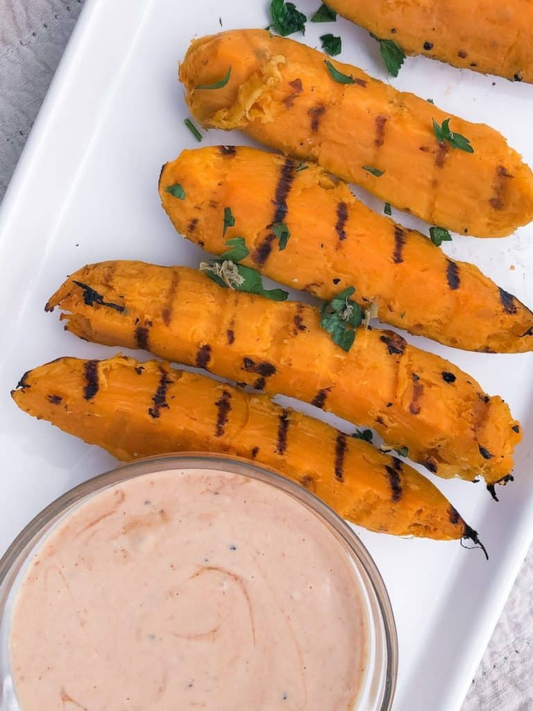 four grilled sweet potato fries with green parsley on a white plate with a bowl of dipping sauce