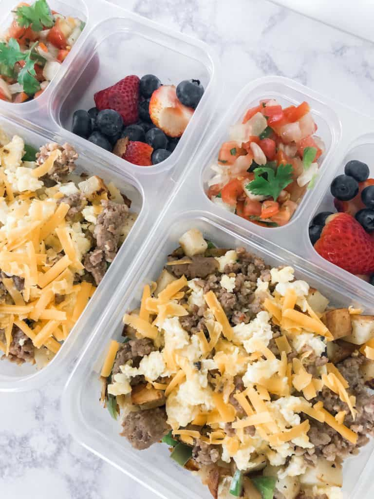 make ahead breakfast bowls with sausage, potatoes, scrambled eggs, vegetables and cheese. Pico de gallo and fresh berries on the side.