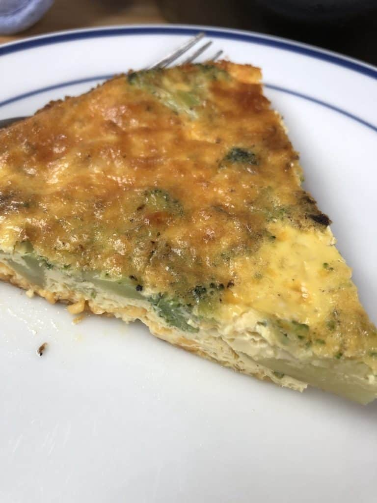 slice of low carb crustless quiche with bacon broccoli and cheese