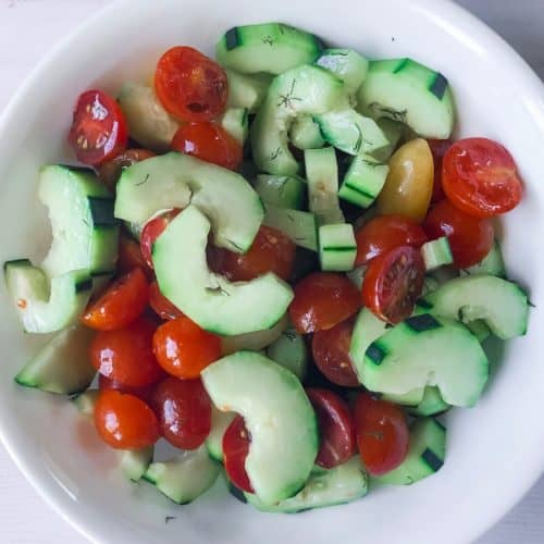 cucumber and tomato salad with dill in a serving bowl.