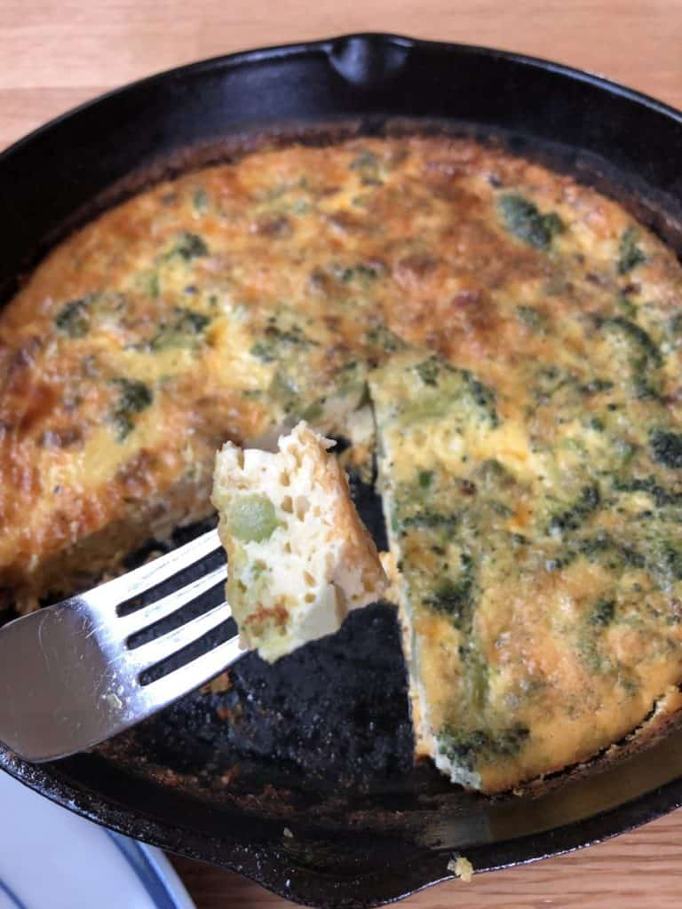 cast iron pan with a bite of crustless quiche