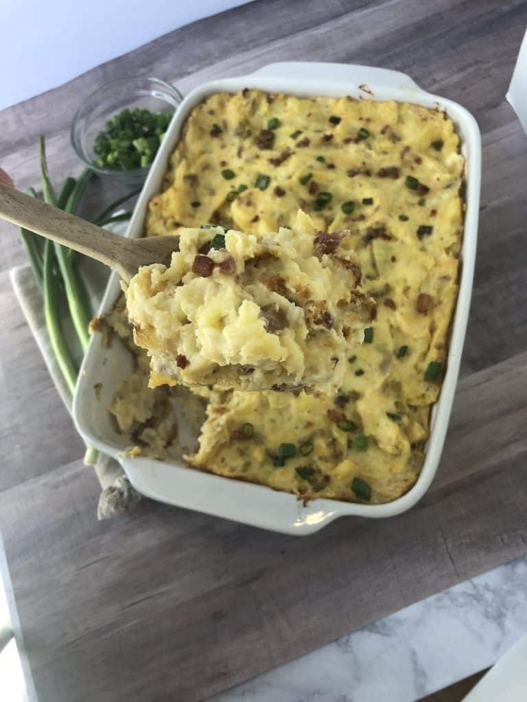 wooden spoon loaded with potatoes, bacon and green onion scooping out of a casserole dish.