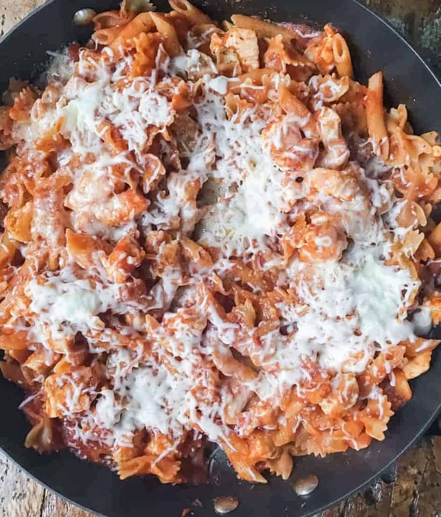skillet filled with pasta, chicken and tomato sauce topped with cheese