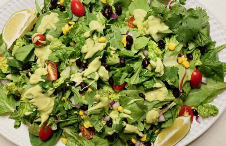 chopped greens with tomato, red onion, and corn topped with creamy avocado dressing