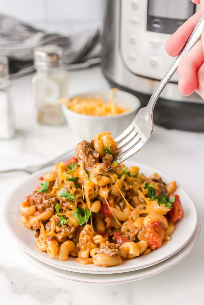 instant pot chili mac on a fork with cheese stringing